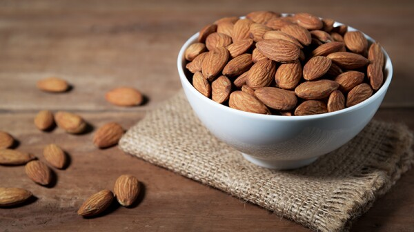 A close-up view of a bowl of almonds on a wooden table