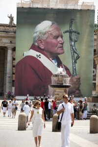 Tourists walking  in St. Peter's Square in front of the manifest with the face of Pope John Paul II