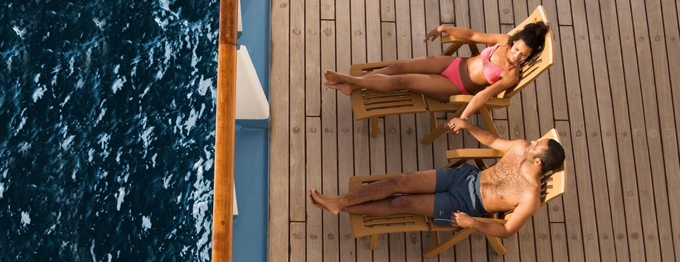 Couple laying on chairs on cruise deck