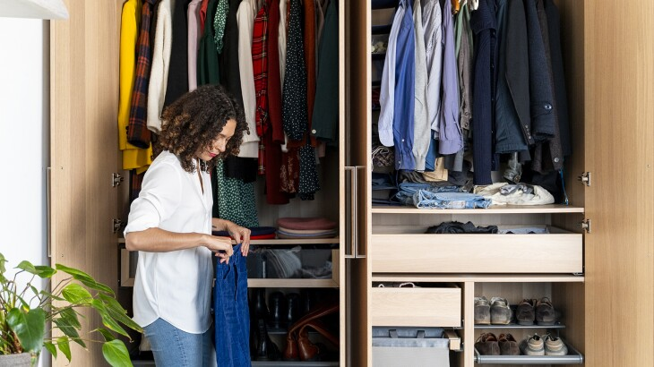 image_of_woman_holding_clothes_in_front_of_closet_GettyImages-1223861343_1800