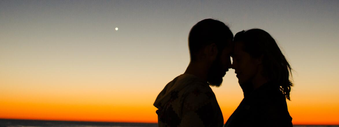 couple embracing in front of sunset