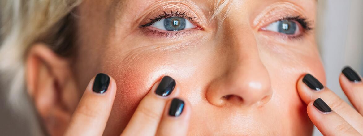 Woman In Her 40s touching her face gently