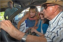 Picture of Am Goyer with her father behind the wheel testing out a new car.