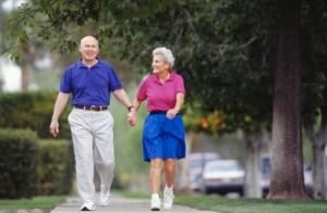 Senior couple walking side by side on sidewalk
