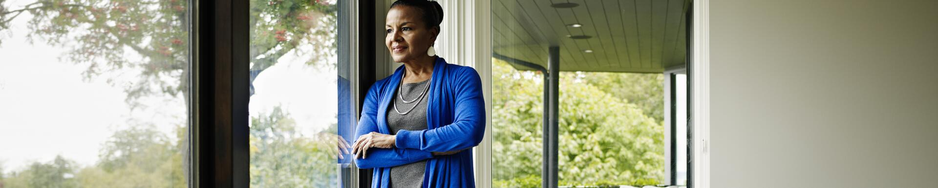 Woman standing arms crossed looking out window