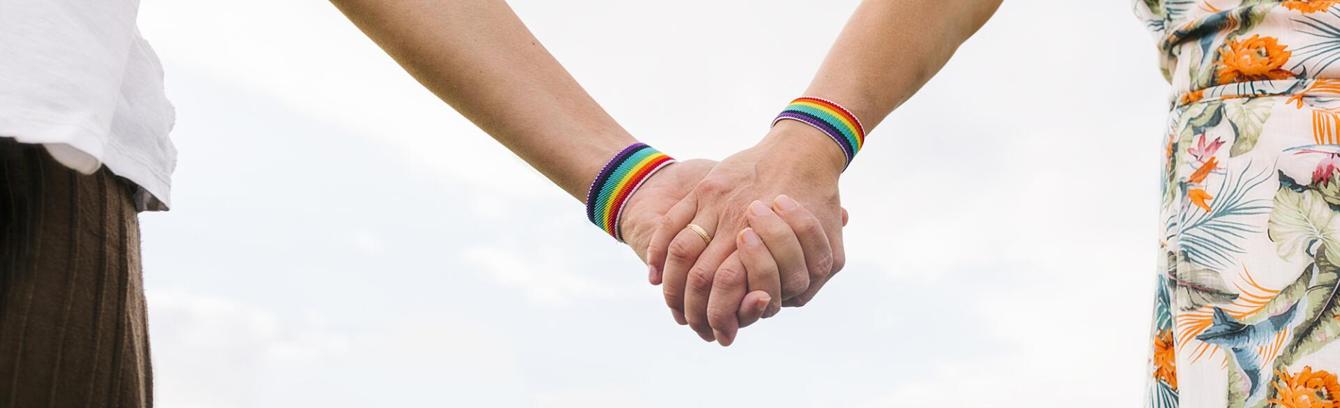 Two women holding hands each wearing a rainbow bracelet and one with a wedding band on