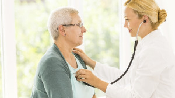 Female doctor listening to senior patient's heart.