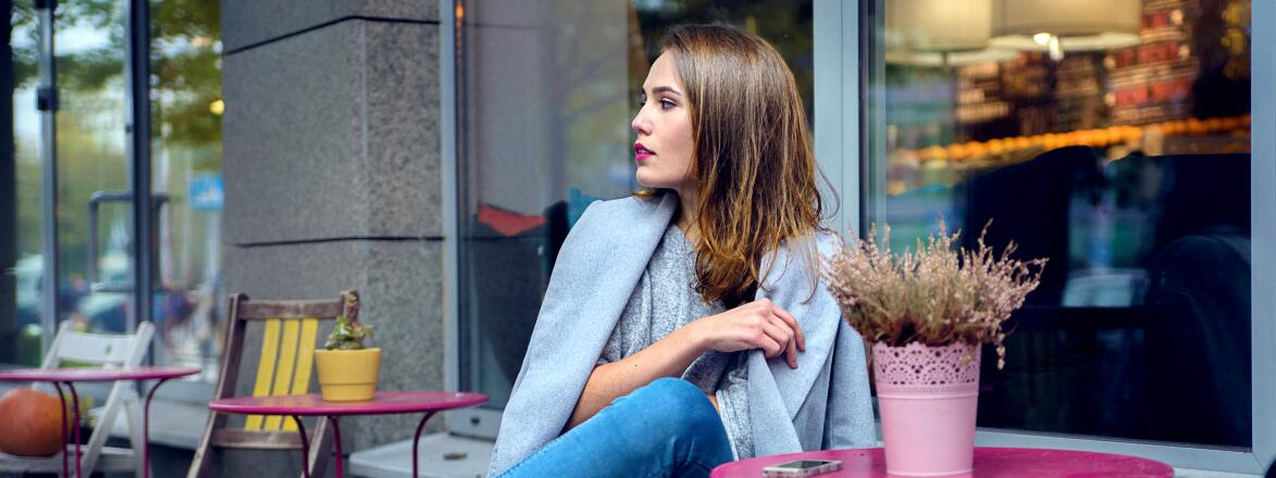 A woman in grey coat and blue jeans is waiting for someone at the cafe