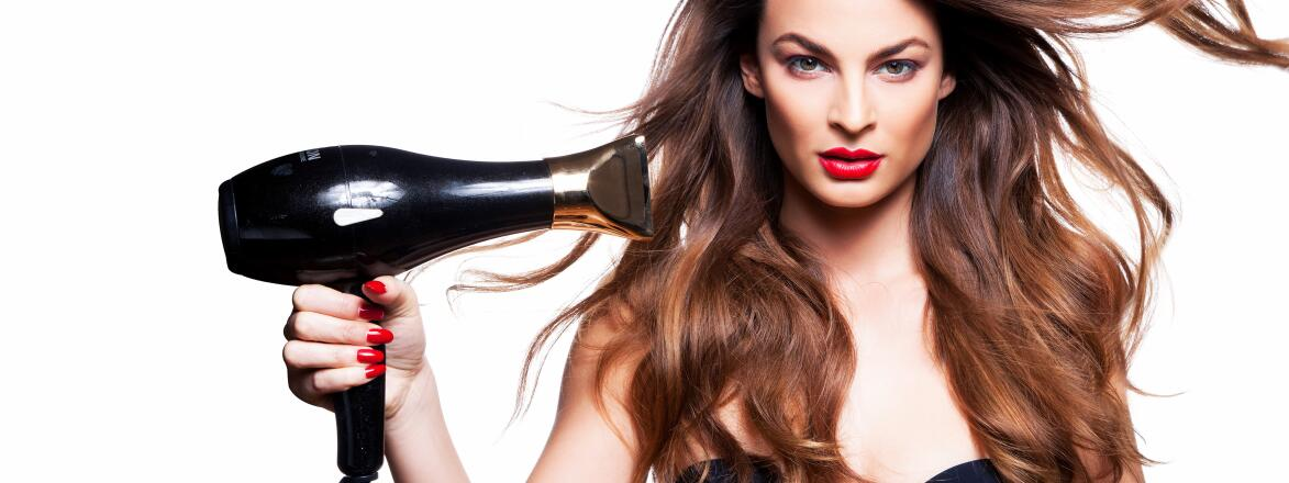 A brunette woman blows her curled hair with a hair dryer