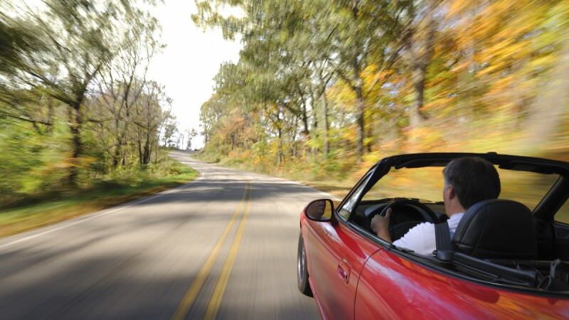 mature man in red convertible on a fall road trip