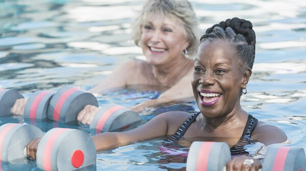 Two smiling women doing water aerobics in a pool