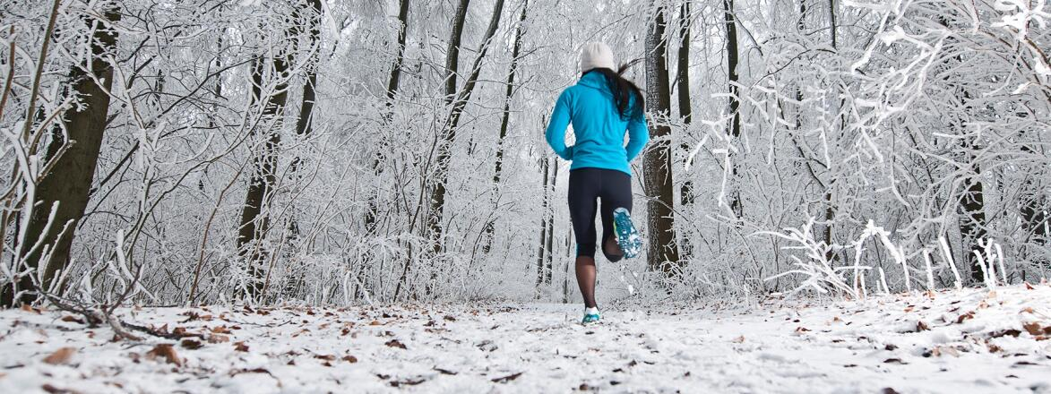 african american woman jogging in a snowy forest