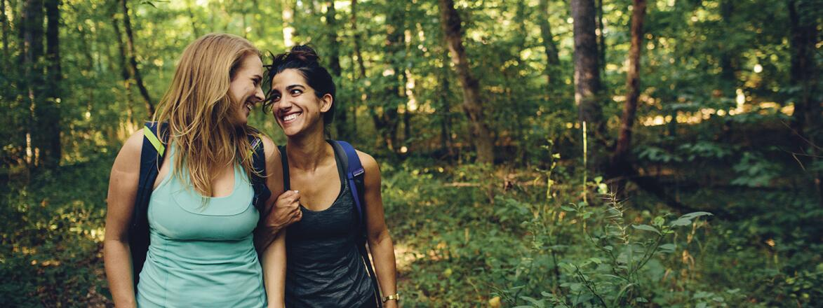 Two women best friends on a hike in the woods.