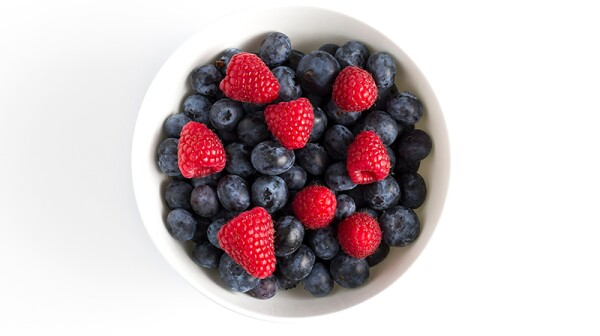 A bowl of blueberries and strawberries against a white background