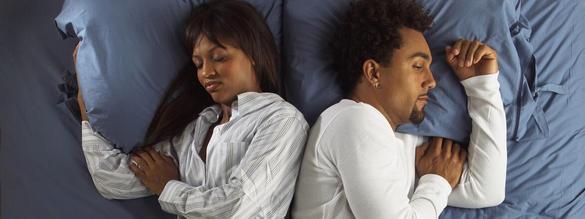 couple lying back to back in bed