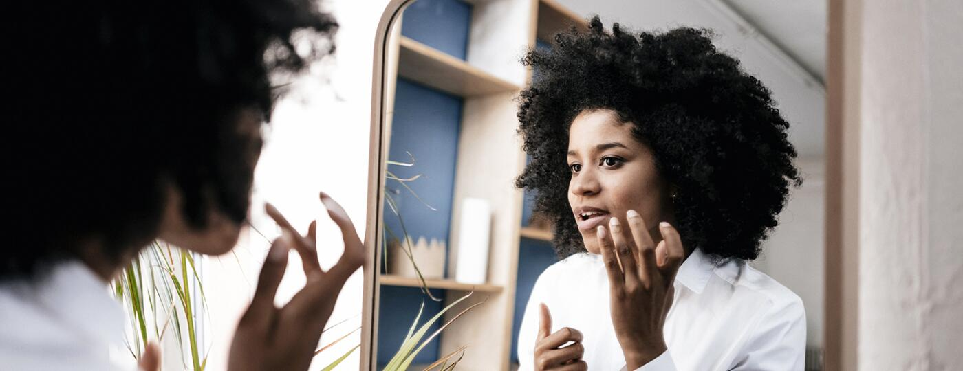 Woman looking in mirror at a dark spot on her face.