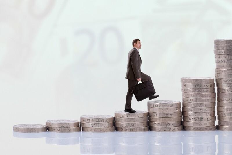 Businessman climbing money stairs
