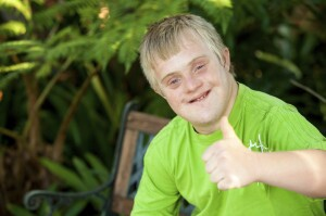 Cute handicapped boy showing thumbs up outdoors