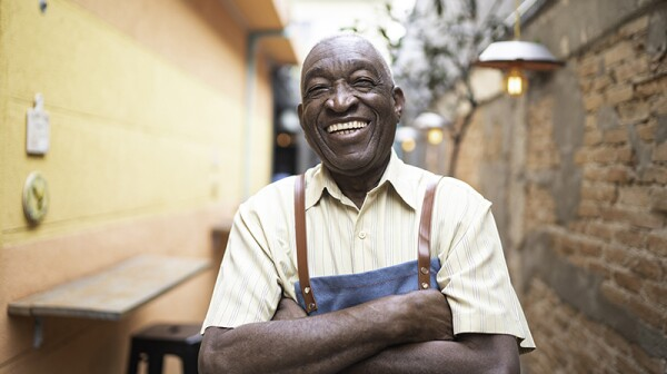 A smiling waiter standing outside