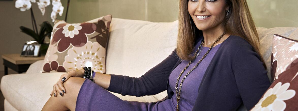 Maria Shriver posing on couch in purple dress