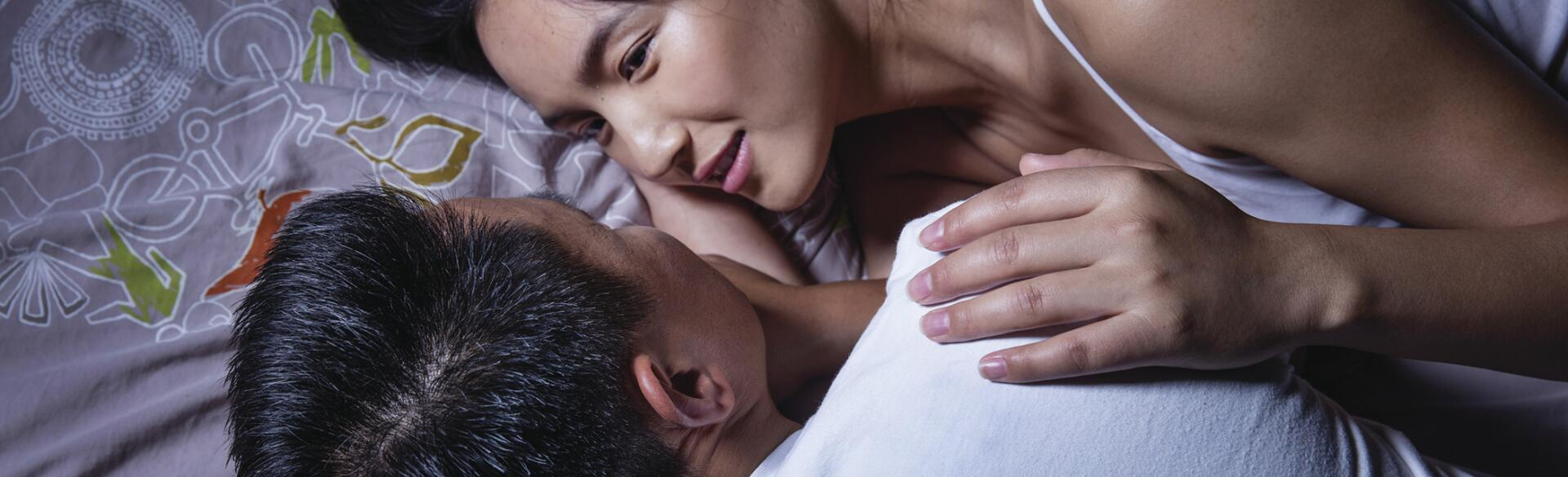 asian couple in bed