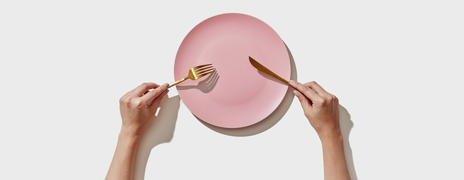 An image of a person holding a fork and knife over an empty plate.