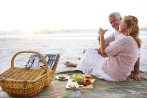 Happy senior couple seated on the beach and enjoying a picnic