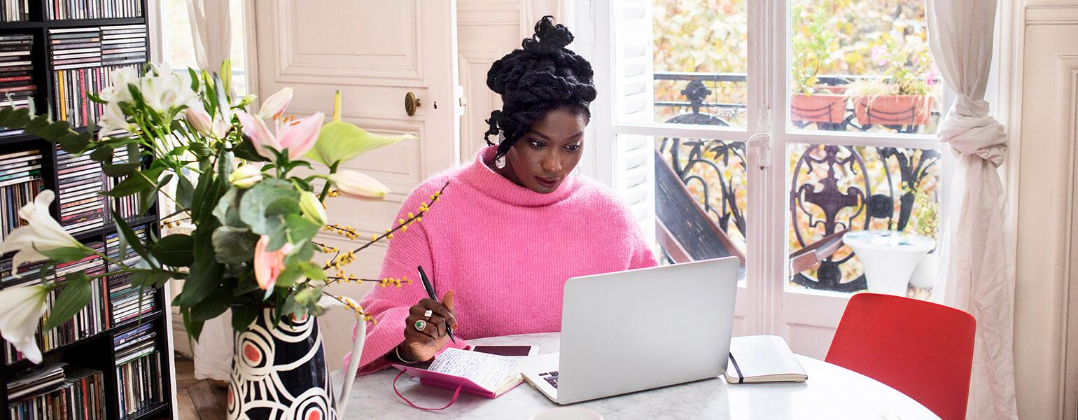 image_of_black_woman_sitting_at_table_working_on_laptop_GettyImages-1063295912_1540.jpg