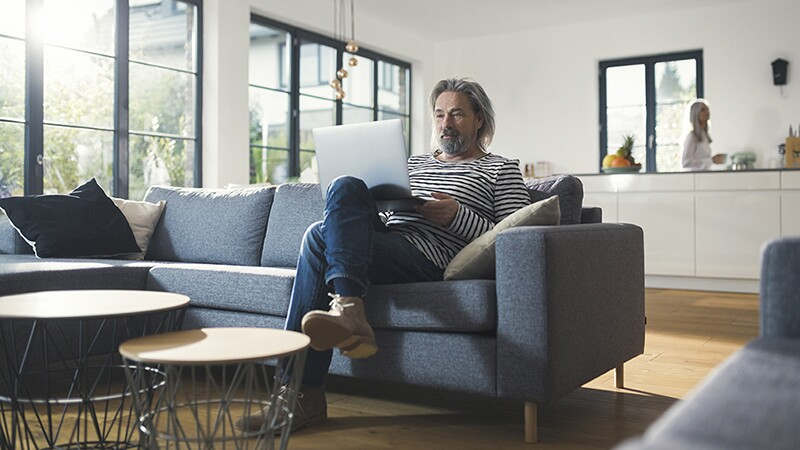 A man sitting on a couch with a laptop on his lap