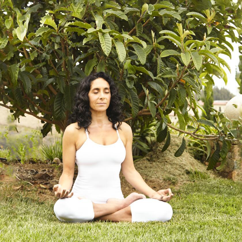 Mandy Ingber does yoga exercises outside.