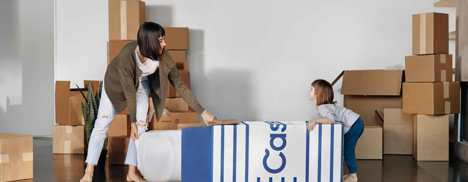 mother and daughter opening casper mattress box at home