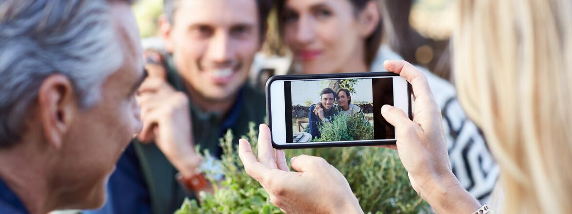 couple taking a photo of another couple on a smartphone