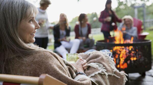 women relaxing around fire pit in backyard