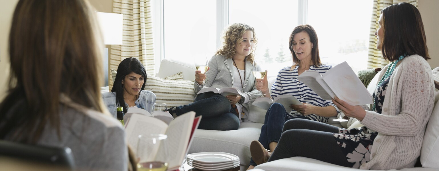 Mature female friends with wine glasses and books at a book club