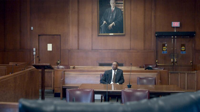 Sean Ellis sits in a courtroom in a still from the documentary Trial 4.