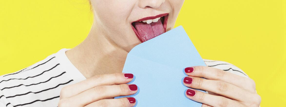 An image of a woman licking a letter envelope.