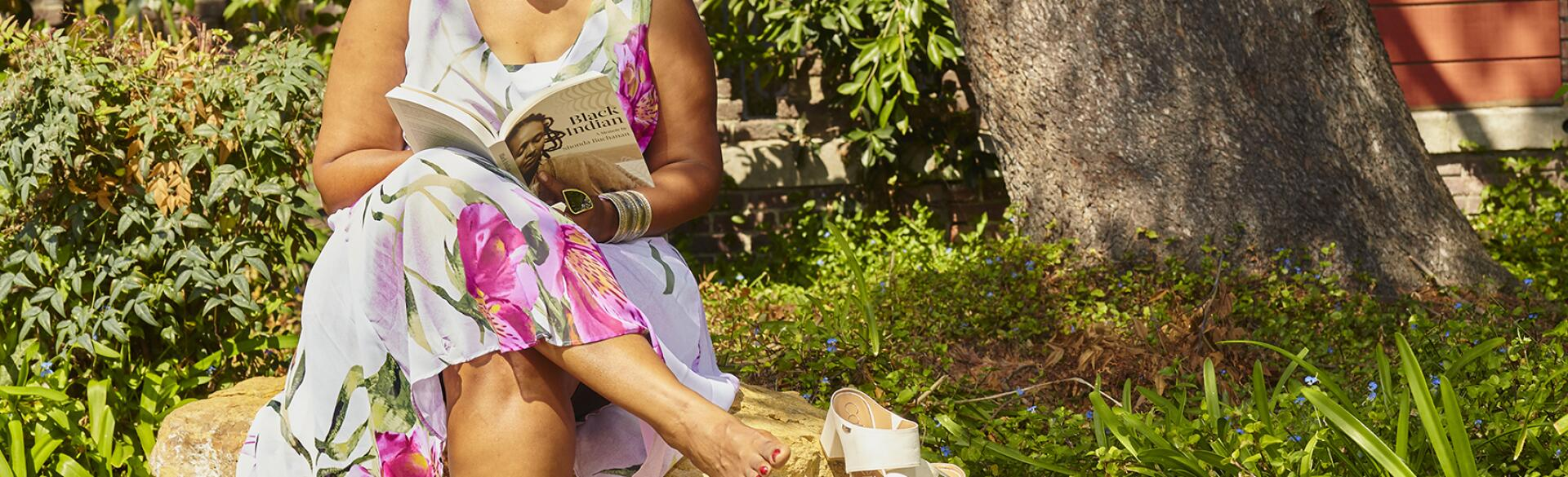 Shonda Buchanan sitting on a park bench reading her book titled Black Indian