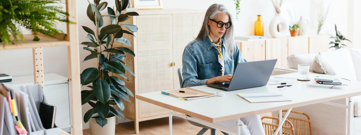 Middle Aged Woman Using Laptop In Home Office