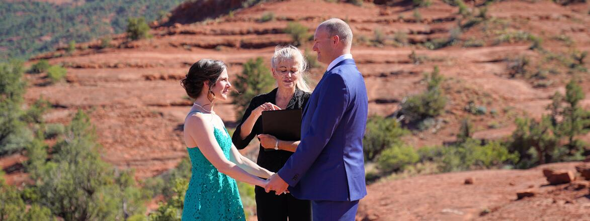 A couple with their officiator standing on red rocks for their private wedding ceremony