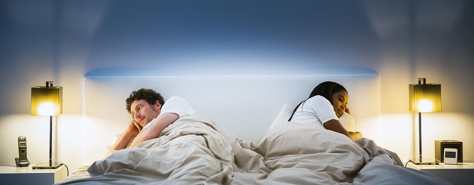 couple lying in bed facing opposite directions