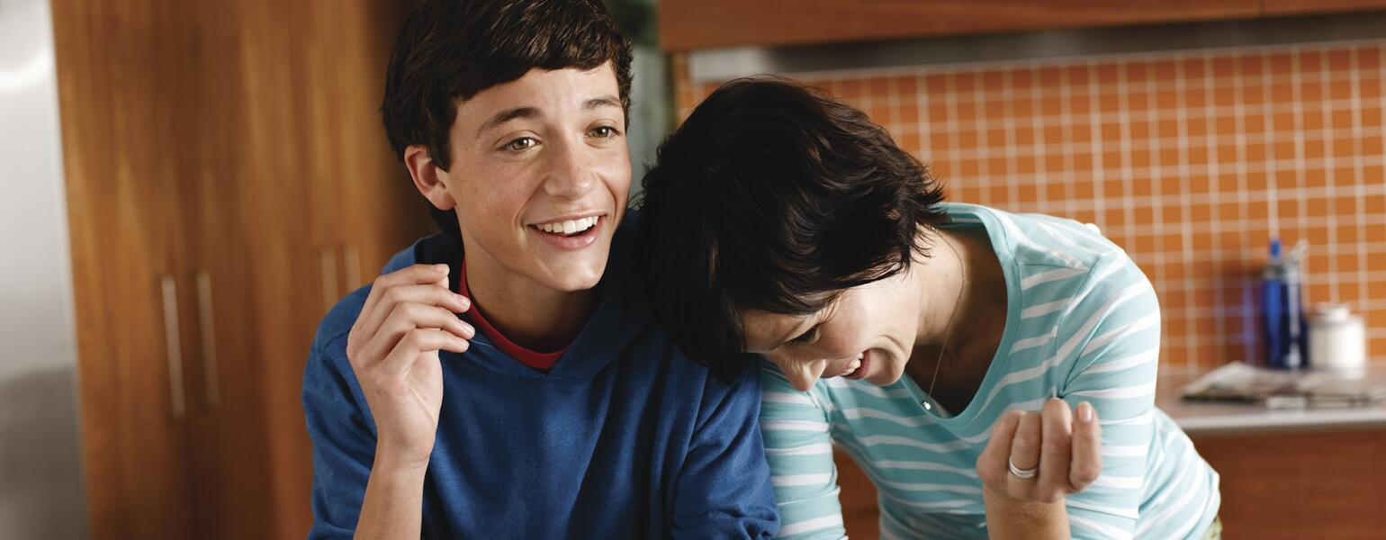 Mother and her teenage son laughing in their kitchen