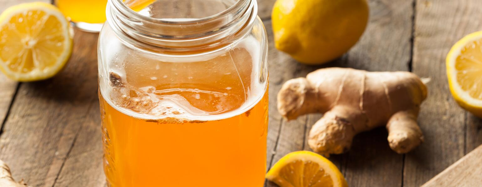 Kombucha in a mason jar surrounded by ginger lemon and oranges
