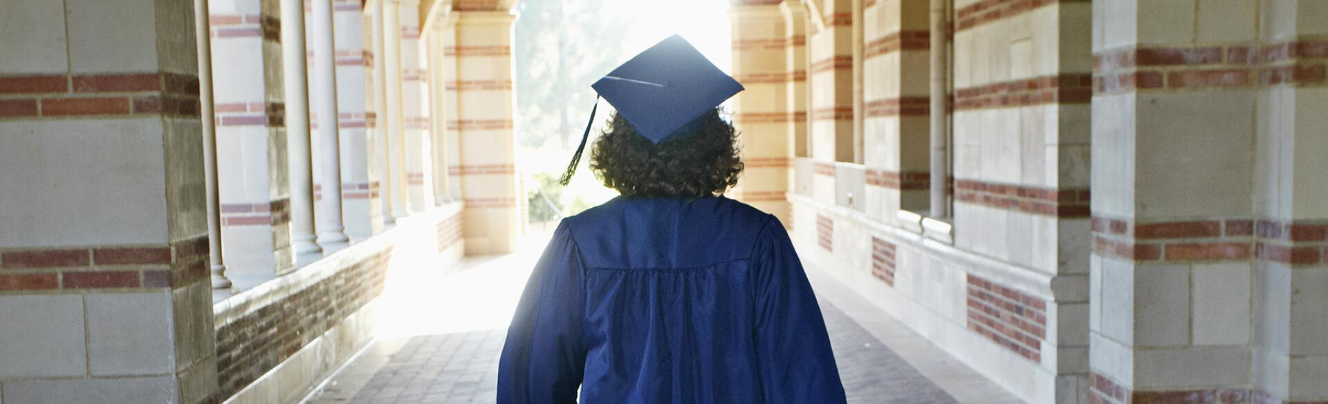 image_of_woman_in_graduate_robe_walking_from_behind_GettyImages-162749395_1800