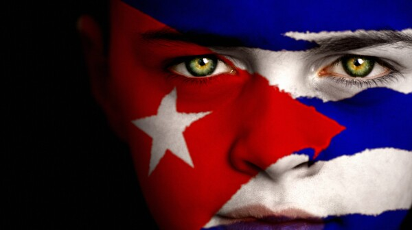 Portrait of a boy with the flag of cuba painted on his face.