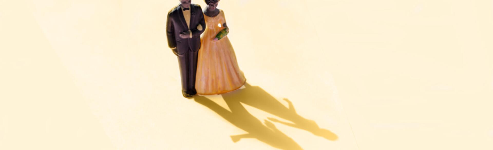 wedding cake topper of couple with shadow showing couple separate
