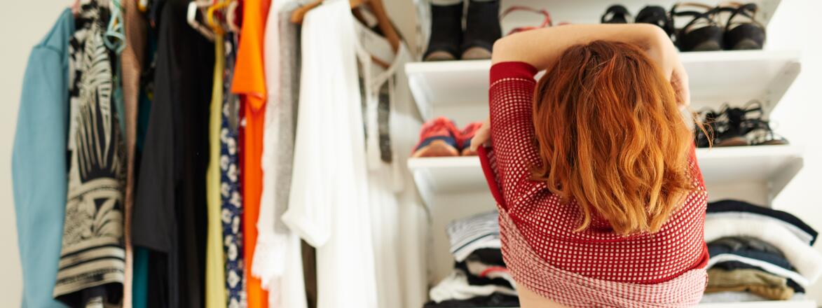 Red headed woman changing in front of a closet