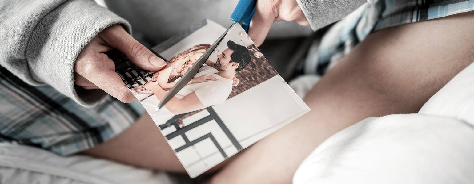 woman cutting photo of her and her ex in half