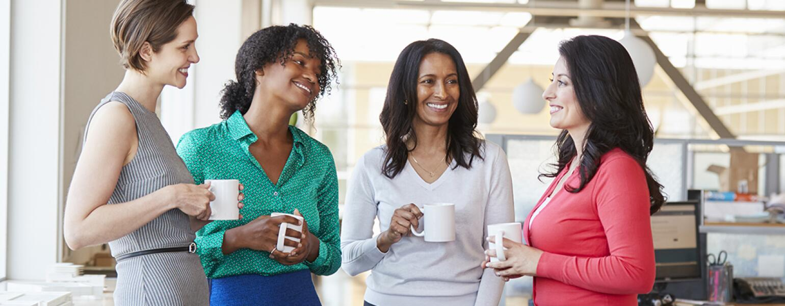 group of 4 women friends talking and drinking coffee