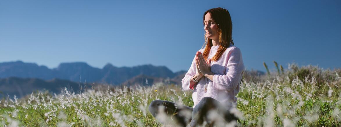 Beautiful Young Woman Meditates In Grassland With Mountains In The Background