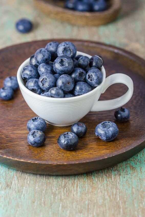 Blueberries in a cup on a wooden table.